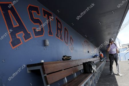 Brian Cashman, general manager of the New York Yankees, talks on the phone in the the dugout prior to a spring training baseball game against the Washington Nationals, in West Palm Beach, Fla