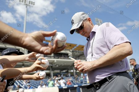 Brian Cashman, right, general manager of the New York Yankees, signs autographs for fans prior to a spring training baseball game against the Washington Nationals, in West Palm Beach, Fla