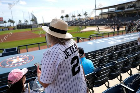 Woman wears a Derek Jeter as she settles into her seat prior to a spring training baseball game between the New York Yankees and the Washington Nationals, in West Palm Beach, Fla