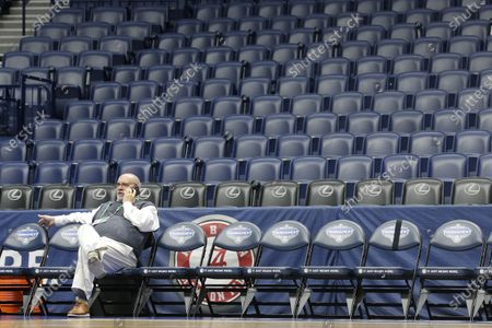 Rob Thomas, a contractor responsible for signage, talks on the phone as he sits in a team bench area in Bridgestone Arena at the site of the NCAA college basketball Southeastern Conference tournament, in Nashville, Tenn. The tournament was cancelled Thursday due to coronavirus concerns. The vast majority of people recover from the new coronavirus. According to the World Health Organization, most people recover in about two to six weeks, depending on the severity of the illness