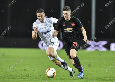 Manchester United's Daniel James, right, and LASK's James Holland challenge for the ball during the Europa League round of 16 first leg soccer match between Linzer ASK and Manchester United in Linz, Austria, . The match is being played in an empty stadium because of the coronavirus outbreak