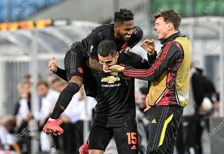 Manchester United's Fred jumps on Manchester United's scorer Andreas Pereira who scored his side's 5th goal during the Europa League round of 16 first leg soccer match between Linzer ASK and Manchester United in Linz, Austria, . The match is being played in an empty stadium because of the coronavirus outbreak