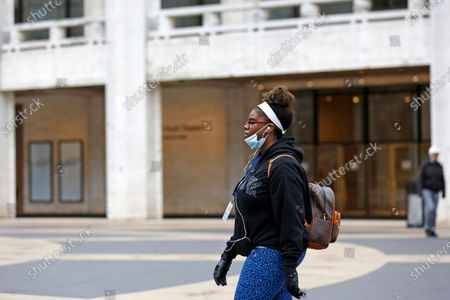 Stock Picture of Woman wearing a mask walks past the David Koch Theatre in Lincoln Center, most of which is closed through the end of March, in New York. The closings came in the wake of a statewide ban on gatherings of more than 500 people, announced by New York Gov. Andrew Cuomo amid a rise in coronavirus cases. For most people the new coronavirus causes only mild or moderate symptoms, such as fever and cough. For some, especially older adults and people with existing health problems, it can cause more severe illness including pneumonia