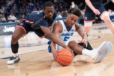 St. John's guard Greg Williams Jr., left, and Creighton guard Ty-Shon Alexander (5) reach for a loose ball in the first half of an NCAA college basketball game in the quarterfinals of the Big East Conference men's tournament, at Madison Square Garden in New York. The tournament was cancelled at halftime due to coronavirus concerns