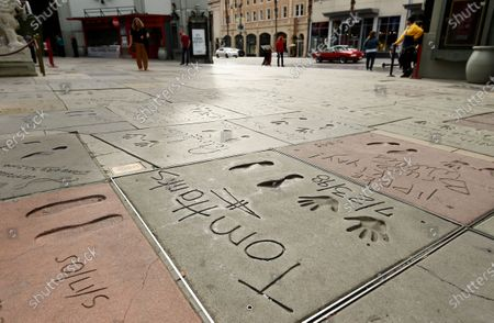 The cement inscription of actor Tom Hanks sits in the nearly empty forecourt of the TCL Chinese Theatre, in the Hollywood section of Los Angeles. Hanks and his wife, actress-singer Rita Wilson, have tested positive for the coronavirus, the actor said in a statement Wednesday. For most people, the new coronavirus causes only mild or moderate symptoms. For some it can cause more severe illness