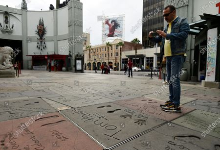 Man takes a picture of the hand and footprints of actor Tom Hanks in the forecourt of the TCL Chinese Theatre, in the Hollywood section of Los Angeles. Hanks and his wife, actress-singer Rita Wilson, have tested positive for the coronavirus, the actor said in a statement Wednesday. For most people, the new coronavirus causes only mild or moderate symptoms. For some it can cause more severe illness