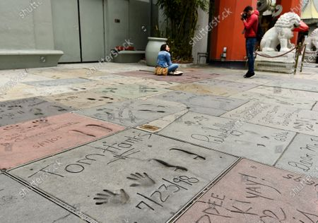 Visitors take pictures near the cement inscription of actor Tom Hanks in the forecourt of the TCL Chinese Theatre, in the Hollywood section of Los Angeles. Hanks and his wife, actress-singer Rita Wilson, have tested positive for the coronavirus, the actor said in a statement Wednesday. For most people, the new coronavirus causes only mild or moderate symptoms. For some it can cause more severe illness
