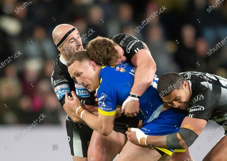 Warrington's Jason Clark is tackled by Hull FC's Danny Houghton, Scott Taylor & Chris Satae.