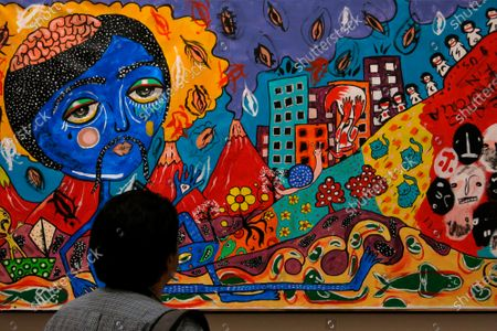 """Member of the press looks at the painting titled """"El Pene"""" by Chilean singer Mon Laferte during a media presentation of the exhibition, """"Gestos"""" or Gestures, at the Museum of Mexico City, . Mon Laferte's nearly 70 works of art showing various techniques including ink, oils and mixed media will be on exhibit from March 12 through April 12"""