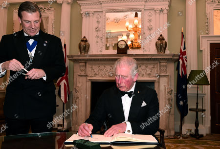 Prince Charles signs a book as he attends a dinner with the Lord Mayor of the City of London, William Russell (L) in aid of the Australian bushfire relief and recovery effort at Mansion House