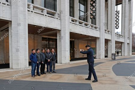 Man takes a group photo in front of David Koch Theater at Lincoln Center, in New York. Shen Yun canceled performances at the theater through March 29 after New York Gov. Andrew Cuomo temporarily banned gatherings of more than 500 people in the state amid a rise in coronavirus cases