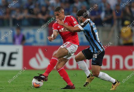 Paolo Guerrero of Brazil's Internacional, left, fights for the ball with Lucas Silva of Gremio during a Copa Libertadores soccer match in Porto Alegre, Brazil