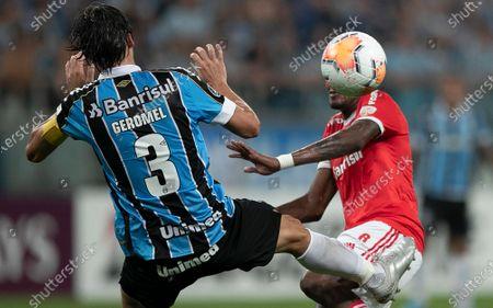 Edenilson of Brazil's Internacional, right, fights for the ball with Pedro Geromel of Gremio during a Copa Libertadores soccer match at Gremio Arena in Porto Alegre, Brazil