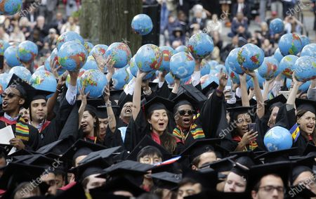 Graduates of Harvard's John F. Kennedy School of Government hold aloft inflatable globes as they celebrate graduating during Harvard University's commencement exercises in Cambridge, Mass. Colleges across the U.S. have begun cancelling and curtailing spring graduation events amid fears that the new coronavirus will not have subsided before the stretch of April and May when schools typically invite thousands of visitors to campus to honor graduating seniors