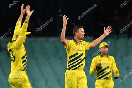 Australia's Josh Hazlewood (C) is denied the wicket of New Zealand's Lockie Ferguson during game 1 of the men's One Day International (ODI) between Australia and New Zealand at the Sydney Cricket Ground (SCG) in Sydney, Australia, 13 March 2020. Cricket Australia decided to close all matches in the ODI series against New Zealand to spectators due to the ongoing coronavirus pandemic.