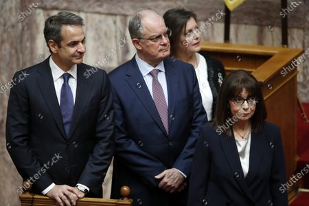 Newly elected Greek President Katerina Sakellaropoulou, right, accompanied by Greece's Prime Minister Kyriakos Mitsotakis, left, and the Spokesman of the Greek Parliament Konstantinos Tasoulas, center, arrives for the swearing-in ceremony at the Greek Parliament in Athens, on . Greece's first female president, a former high court judge, was being formally sworn in to office Friday, nearly two months after the country's parliament voted overwhelmingly to elect her. The swearing in ceremony for Katerina Sakellaropoulou was being held Friday in an almost empty parliament, as part of measures being taken to prevent the spread of the new coronavirus