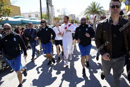"Stock Photo of Actor Gerard Butler runs as a torchbearer during the Olympic torch relay of the 2020 Tokyo Olympic Games in the southern Greek town of Sparta, . Greece's Olympic committee says it is suspending the rest of its torch relay for the Olympic flame due to the ""unexpectedly large crowd"" that gathered to watch despite repeated requests for the public to stay away to prevent the spread of the new coronavirus"