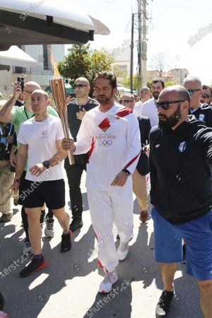 "Actor Gerard Butler runs as a torchbearer during the Olympic torch relay of the 2020 Tokyo Olympic Games in the southern Greek town of Sparta, . Greece's Olympic committee says it is suspending the rest of its torch relay for the Olympic flame due to the ""unexpectedly large crowd"" that gathered to watch despite repeated requests for the public to stay away to prevent the spread of the new coronavirus"