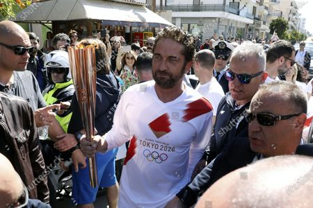 "Stock Image of Actor Gerard Butler runs as a torchbearer during the Olympic torch relay of the 2020 Tokyo Olympic Games in the southern Greek town of Sparta, . Greece's Olympic committee says it is suspending the rest of its torch relay for the Olympic flame due to the ""unexpectedly large crowd"" that gathered to watch despite repeated requests for the public to stay away to prevent the spread of the new coronavirus"