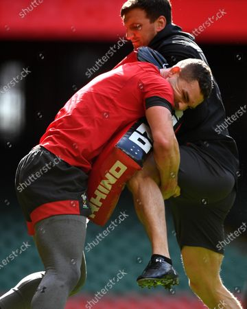 Stock Photo of George North hits a tackle bag held by Sam Warburton during training.