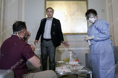 Romania's health minister Victor Costache speaks to health officials called in to take samples for a coronavirus test from journalists and lawmakers in Bucharest, Romania, after it was confirmed that a senator who attended several meetings in the building tested positive for the infection. The caretaker prime minister of Romania, Ludovic Orban, said in a press conference at the parliament, the government, including all ministers, as well as the leadership of the ruling National Liberal Party and all its senators, are going into quarantine after one of the governing party's senators, who took part in high-level meetings, who confirmed to be infected with the coronavirus