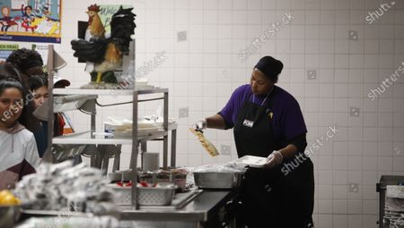 Nicole Johnson prepares lunch for students lined up in the cafeteria at Lincoln High School in Dallas, . During the coming extended spring break school closures, this cafeteria and a few others in the Dallas Independent School District will be providing lunches to students despite the closure of the school