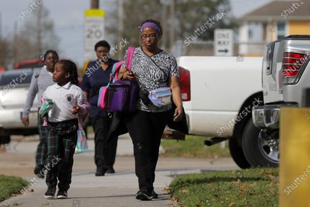 Stock Photo of Danielle Tucker walks with her daughter Mariah Tucker, 5, after school was adjourned at the Dr.Martin Luther King, Jr. Elementary School for Science and Technology in New Orleans, . Louisiana Gov. John Bel Edwards on Friday closed K-12 public schools across the state for roughly a month and banned gatherings of more than 250 people in an effort to slow the spread of the coronavirus. For most people, the new coronavirus causes only mild or moderate symptoms. For some it can cause more severe illness