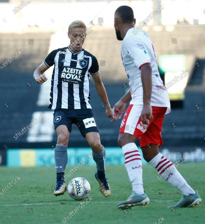 Botafogo's Keisuke Honda, of Japan, left, controls the ball during a Carioca Championship soccer match against Bangu in Rio de Janeiro, Brazil, . The match was played in an empty, closed door stadium to contain transmission of the new coronavirus