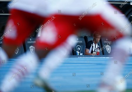 Botafogo's Keisuke Honda, of Japan, looks at Bangu's soccer players from the bench during a Carioca Championship soccer match in Rio de Janeiro, Brazil, . The match was played in an empty, closed door stadium to contain transmission of the new coronavirus