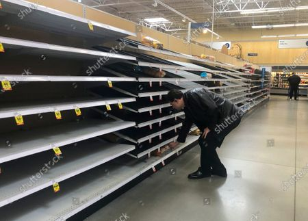 A shopper reaches for one of the few remaining loaves of bread on nearly empty shelves in a grocery store in Round Lake Beach, Illinois, USA, 15 March 2020. In Illinois, Governor J.B. Pritzker has ordered all restaurants, bars and schools to close in response to the coronavirus SARS-CoV-2 which causes the Covid-19 disease. Shoppers have bought up large quantities of water, toilet paper, cleaning and disinfecteing supplies, bread, and other items.