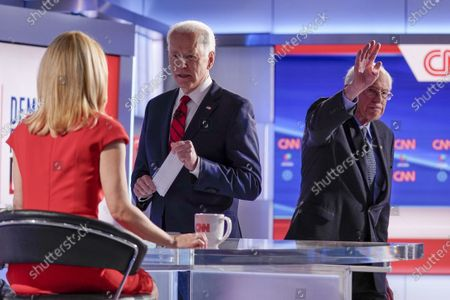 Former Vice President Joe Biden, center, stops to talk with CNN anchor Dana Bash, left, as Sen. Bernie Sanders, I-Vt., right, waves after they participated in a Democratic presidential primary debate at CNN Studios in Washington