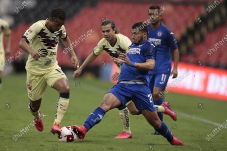 America's Giovani Dos Santos, left, and Cruz Azul's Juan Escobar compete for the ball during a Mexican soccer league match at Azteca stadium in Mexico City, . The match was played behind closed doors as a precaution against the spread of the new coronavirus