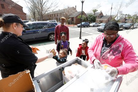 Sarah Richardson, at left, and Cynthia Gourdine, at right, with the nutrition department for the Charleston County School District, delivers some grab and go bags of food for area school children at Sanders-Clyde Elementary School, in Charleston, S.C. With all schools closed in South Carolina to at least the end of March because of the Coronavirus area school district are providing two meals a day to area school children