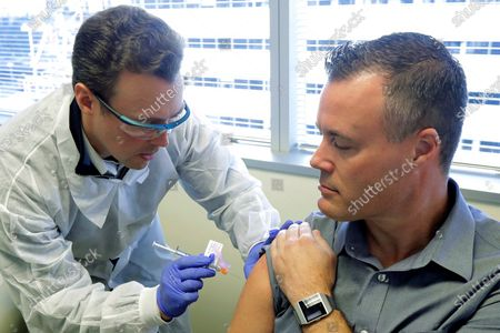 Pharmacist Michael Witte, left, gives Neal Browning a shot in the first-stage study of a potential coronavirus vaccine, at the Kaiser Permanente Washington Health Research Institute in Seattle. Browning is the second patient to receive the shot in the study