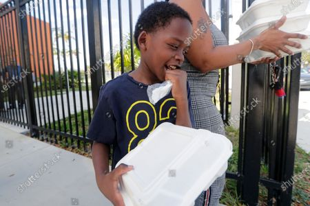 Michael Gordon Williams leaves the Frederick Douglass Elementary School with his mother carrying meals provided by the school, in Miami, Fla. Miami Dade-County Public Schools are providing breakfast and lunch to students in need while schools are closed for the week due to the new coronavirus