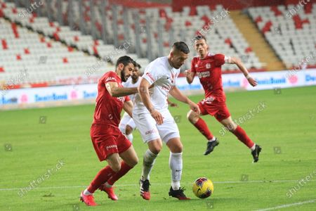 Stock Photo of Antalyaspor's Lukas Podolski, centre, controls the ball during a Turkish Super League soccer match between Antalyaspor and Sivasspor in Antalya, Turkey, . The match was played without spectators because of the coronavirus outbreak. For most people, the new coronavirus causes only mild or moderate symptoms. For some it can cause more severe illness