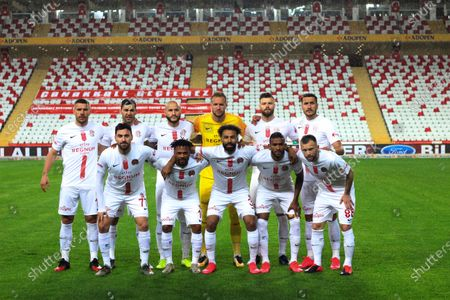 Antalyaspor's team members including Lukas Podolski, left, pose for photos prior to a Turkish Super League soccer match between Antalyaspor and Sivasspor in Antalya, Turkey, . The match was played without spectators because of the coronavirus outbreak. For most people, the new coronavirus causes only mild or moderate symptoms. For some it can cause more severe illness