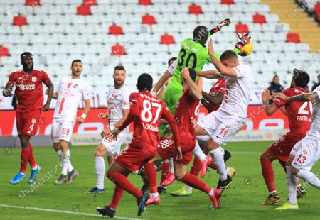 Stock Picture of Antalyaspor's Lukas Podolski, right no 11, jumps for the ball along with Sivasspor's goalkeeper Mamadou Samassa, center no 30, during a Turkish Super League soccer match between Antalyaspor and Sivasspor in Antalya, Turkey, . The match was played without spectators because of the coronavirus outbreak. For most people, the new coronavirus causes only mild or moderate symptoms. For some it can cause more severe illness