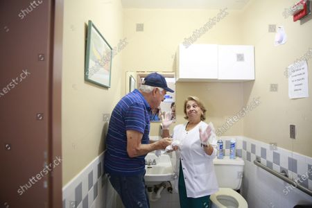 Nursing assistant Maria Castro, right, helps Rene Gonzalez, 84, left, to wash his hands at Little Havana Activities and Nutrition Centers of Dade County, Inc.,, in Miami