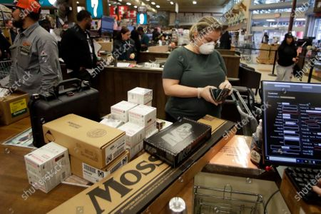 Stephanie Miller of Atlanta, buys guns and ammunition for them at Adventure Outdoors, in Smyrna, Ga. Miller said she had been on the fence about guns but with recent events she decided to buy guns