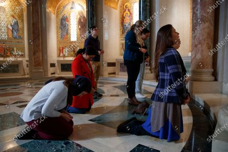 Stock Photo of From left, Grace Hegarty, Fatima Corona, Andrew Klabnik, Savannah Sully, Shideya Parrilla, Natalie Plumb, and Casey Collins, pray the Rosary at the Basilica of the National Shrine of the Immaculate Conception in Washington, Monday, March, 16, 2020. They came together for Collins' birthday and among their prayers of special intention was for all those affected by the coronavirus outbreak. The Basilica has suspended the public celebration fo mass and there is no scheduled confession, but the doors are open private prayer from 9 a.m. to 5 p.m