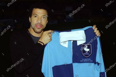 Stock Image of American singer songwriter, composer, Lionel Richie holds up a Wycombe Wanderers shirt ahead of kick-off as he walked around the ground meeting fans during Wycombe Wanderers vs Notts County, Nationwide League Division Two Football at Adams Park on 6th October 2000