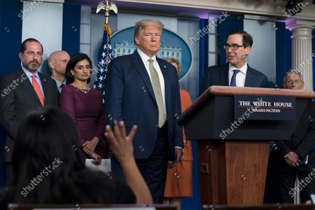 President Donald Trump and Treasury Secretary Steven Mnuchin, right, listen to a question during a press briefing with the coronavirus task force, at the White House, in Washington. Listening from left are Health and Human Services Secretary Alex Azar, Stephen Hahn, commissioner of the Food and Drug Administration, Administrator of the Centers for Medicare and Medicaid Services Seema Verma and Dr. Deborah Birx, White House coronavirus response coordinator, and Dr. Anthony Fauci, director of the National Institute of Allergy and Infectious Diseases