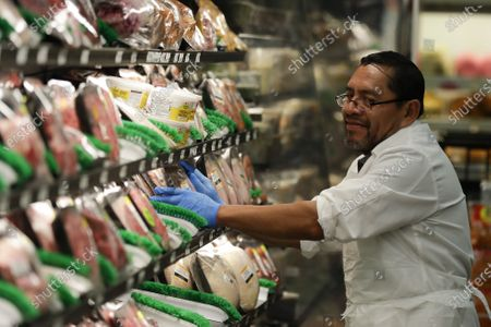 Stock Picture of Jose Perez stocks meat wearing rubber gloves at Northgate González Market, in Santa Ana, Calif. In light of the coronavirus concerns the Northgate market chain opened the store one hour early for seniors 65-years and older and disabled