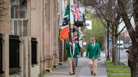 Stock Image of Sinn Fein Society members Bill Bradley, left, and John Lowenthal, right, walk the sidewalk of the St. Patrick's Day parade route in downtown Savannah, Ga., . Last week, Savannah's mayor announced the city's 196-year-old St. Patrick's Day parade was called off due to coronavirus concerns