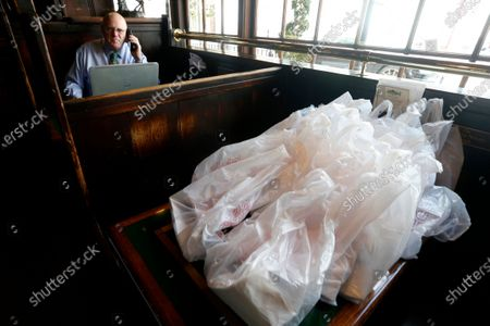 Billy Martin, Owner of Martin's Tavern, works in his restaurant next to a table prepped for takeout orders in the Georgetown neighborhood, in Washington. St. Patrick's Day is his busiest day of the year and he is only running a takeout service