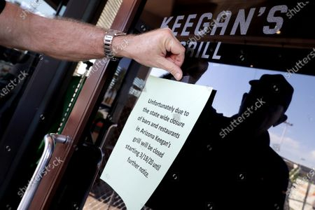 Owner Steve Johnson attaches a notice on the door of Keegan's Grill, in Phoenix notifying guests his restaurant will closing in compliance with the state of emergency issued by the city of Phoenix earlier in the day that restaurants only serve take-out. Phoenix, Tucson and Flagstaff have ordered bars, gyms and other indoor facilities to close immediately and restaurants to offer to-go service only in an effort to slow the spread of the coronavirus