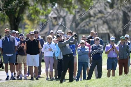 Jimmy Walker, center, hits from from the rough alongside the first fairway during the third round of the Arnold Palmer Invitational golf tournament, in Orlando, Fla