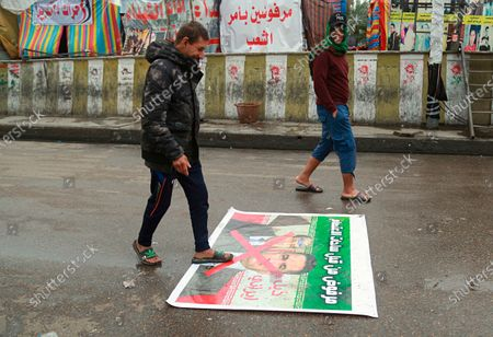 """Stock Photo of Anti-government protesters walk over a defaced poster of former Prime Minister Nouri al-Maliki and Prime Minister-designate Adnan Al-Zurfi with Arabic text reading """"Rejected, Iranian tail, Iran followers"""" in Tahrir Square, Baghdad, Iraq, . Iraq's president named Al-Zurfi as prime minister-designate, following weeks of political infighting and a looming crisis amid a global pandemic"""
