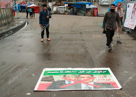 """Anti-government protesters pass by a defaced poster with pictures of former Prime Minister Nouri al-Maliki, left, and Prime Minister-designate Adnan Al-Zurfi witg Arabic text reading """"Rejected, Iranian tail, Iran followers"""" in Tahrir Square, Baghdad, Iraq, . Iraq's president named Al-Zurfi as prime minister-designate, following weeks of political infighting and a looming crisis amid a global pandemic"""